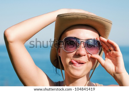 Portrait of a pretty happy young woman enjoying at a beach - stock photo