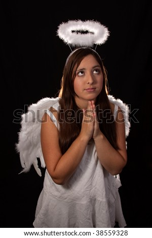 Portrait of a pretty hispanic teen age girl with long brown and eyes wearing a white angel costume with wings and halo praying