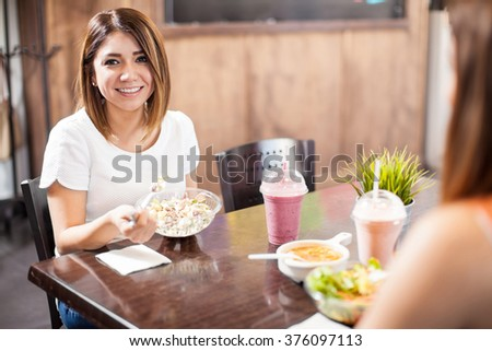 Portrait of a pretty Hispanic young woman eating healthy food with a friend