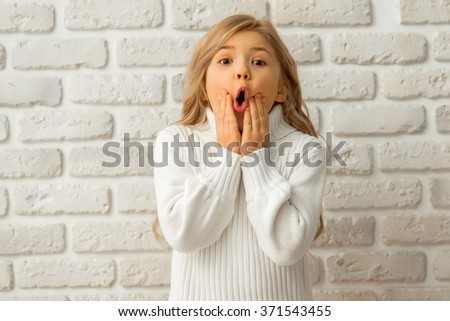 Portrait of a pretty little blonde girl showing emotions while standing against white brick wall