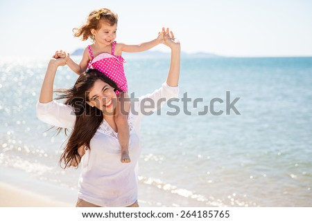 Portrait of a pretty little girl piggyback riding her mother while spending the day in the beach
