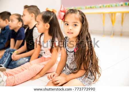 Portrait of a pretty little girl sitting on the floor during class and making eye contact
