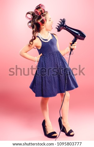 Portrait of a pretty little girl with curlers in her hair holding hair dryer. Studio shot over pink background. Kid's fashion.  #1095803777