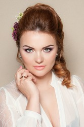 Portrait of a pretty red haired woman with wedding makeup and bridal hair, isolated