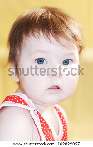 Portrait of a pretty serious little girl with red hair and green eyes. Face close-up, selective focus to the eyes of a baby.