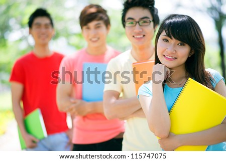 Portrait of a pretty student with her male classmates standing behind