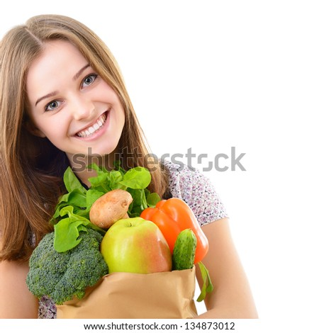 Portrait of a pretty teen girl holding a grocery bag and smiling against white background