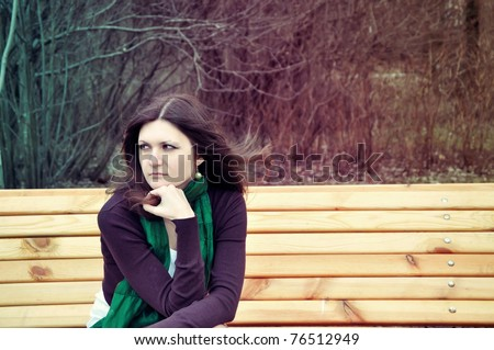 portrait of a pretty thoughtful lady sitting on a banch in a park with artistic colors and shadows added
