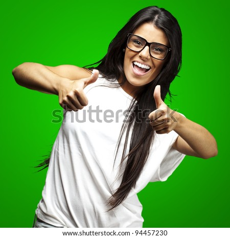 portrait of a pretty woman doing approve symbol over green background