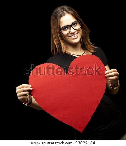 portrait of a pretty woman holding a paper heart against a black background