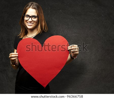 portrait of a pretty woman holding a paper heart against a grunge wall