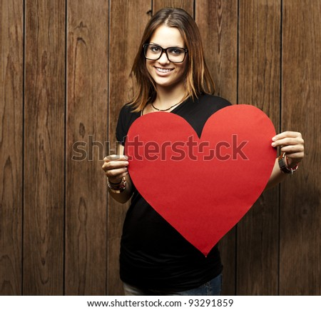portrait of a pretty woman holding a paper heart against a wooden wall