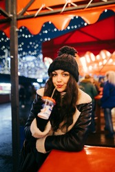 Portrait of a pretty woman in winter clothes standing at a table at a holiday fair and drinking a warming drink from a cup. Vertical portrait of a lady spending time at Christmas on the street.