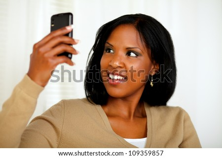 Portrait of a pretty woman reading a message on cellphone at home indoor