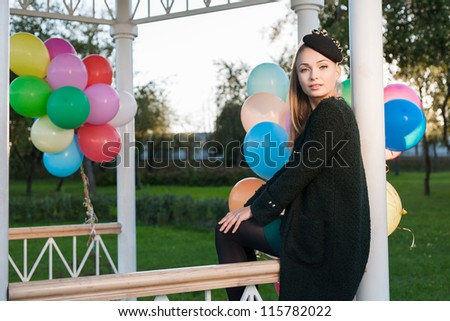 Portrait of a pretty woman sitting in a park against the sunset, outdoors