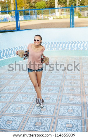 Portrait of a pretty woman with a skateboard in her hand, outdoors