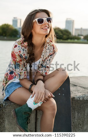 Portrait of a pretty woman with a skateboard, outdoors