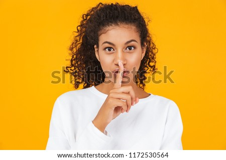 Portrait of a pretty young african woman standing isolated over yellow background, showing silence gesture