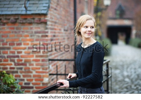 Portrait of a pretty young blond woman standing on a bridge in medieval city quorter and turning back