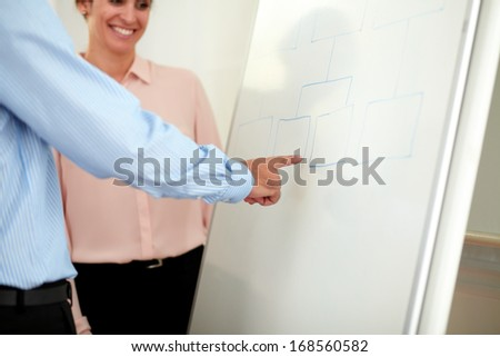 Portrait of a pretty young businesswoman on pink shirt looking at whiteboard with colleagues - copyspace
