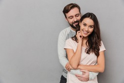 Portrait of a pretty young couple hugging and looking at camera with copy space over gray background