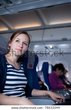 Portrait of a pretty young female passenger on board of an aircraft while on the flight