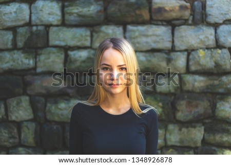 Portrait of a pretty young girl at stone wall close up. Portrait pretty young girl near gray stone wall.  Soft focus.