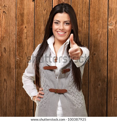 portrait of a pretty young girl doing a good gesture against a wooden wall