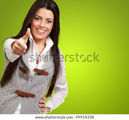 portrait of a pretty young girl doing a good gesture over a green background