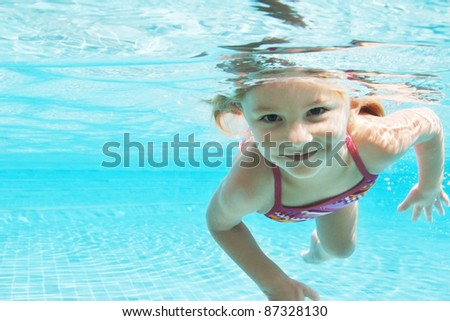 Portrait of a pretty young girl enjoying a swim on a hot day looking at you