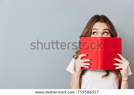 Portrait of a pretty young girl hiding behind an open book and looking away isolated over gray wall background