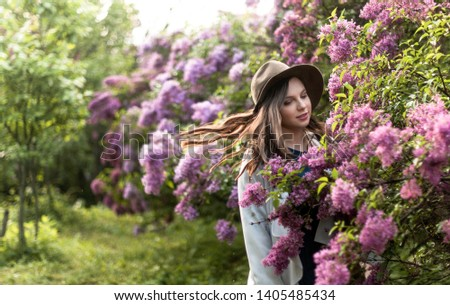 portrait of a pretty young girl in a hat in the bushes of lush lush blossoms #1405485434