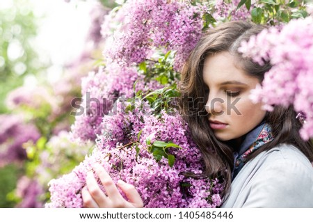 portrait of a pretty young girl in the bushes of lush lush blossoms #1405485446