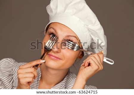 Portrait of a pretty young smiling  uniformed female Chef looking through forks