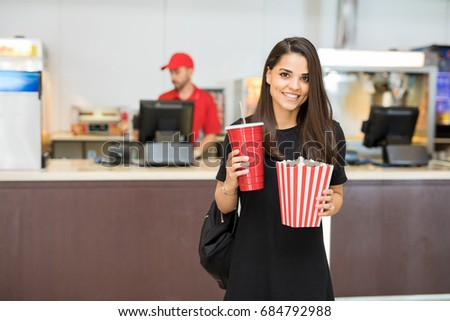 Stock Photo Portrait of a pretty young woman carrying some snacks in a movie theater and smiling