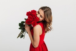 Portrait of a pretty young woman dressed in red dress holding bouquet of roses isolated over white background