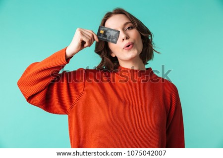 Portrait of a pretty young woman dressed in sweater holding credit card at her face isolated over blue background
