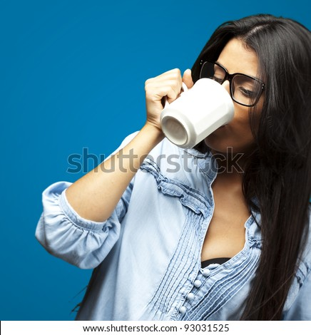 portrait of a pretty young woman drinking coffee on a cup against a blue background