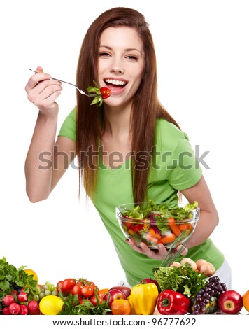 Portrait of a pretty young woman eating vegetable salad against white background