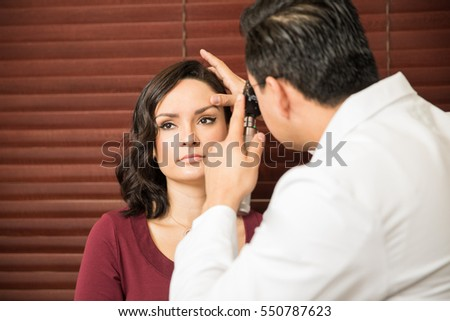 Portrait of a pretty young woman getting her eyes examined by a doctor