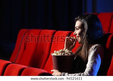 portrait of a pretty young woman, she  eats popcorn and smiles