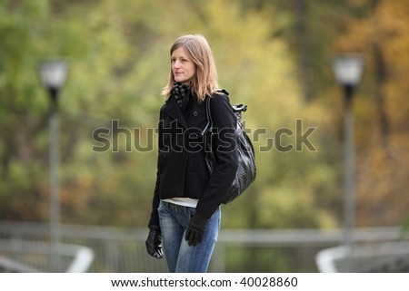 Portrait of a pretty young woman standing in a park on a lovely autumn day