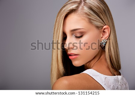 Portrait of a pretty young woman with long blond hair and closed eyes on gray background