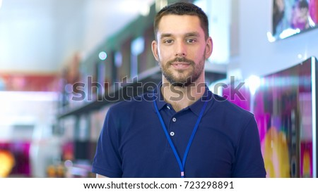 Portrait of a Professional Expert Consultant Smiles and Looks into Camera as Stands in the Bright, Modern Electronics Store Full of Latest Models of TV Sets, Cameras, Tablets and other Devices. Stock photo ©