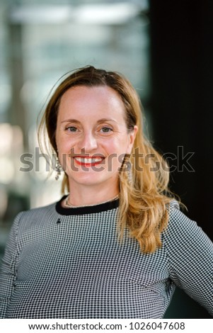 Portrait of a professional, neat and well put-together Caucasian woman in her office of glass and marble. She is smiling and relaxed, confident and cheerful. #1026047608