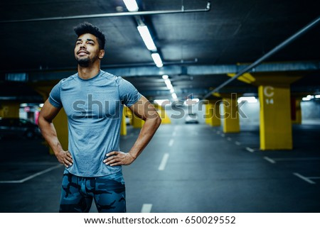 Portrait of a proud african american athlete man holding his hands on hips.
