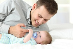 Portrait of a proud father playing with his baby son on a bed at home