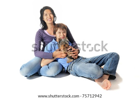 portrait of a purebred yorkshire terrier and asian family in front of white background