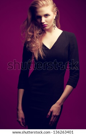 Portrait of a red-haired (ginger) fashionable model in a black classic cocktail dress posing over purple background. Seductive glance. Vogue style. Studio shot