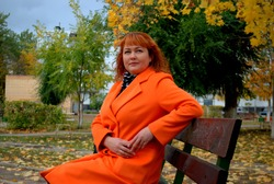 Portrait of a red-haired girl sitting on a bench in an orange coat against the background of bright autumn trees